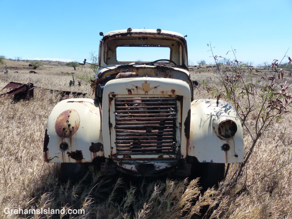 An old truck sits abandoned in a dry field.