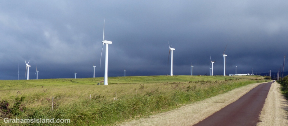 Dark clouds roll across the Kohala Mountains providing a dramatic backdrop to the turbines of Hawi Wind Farm.