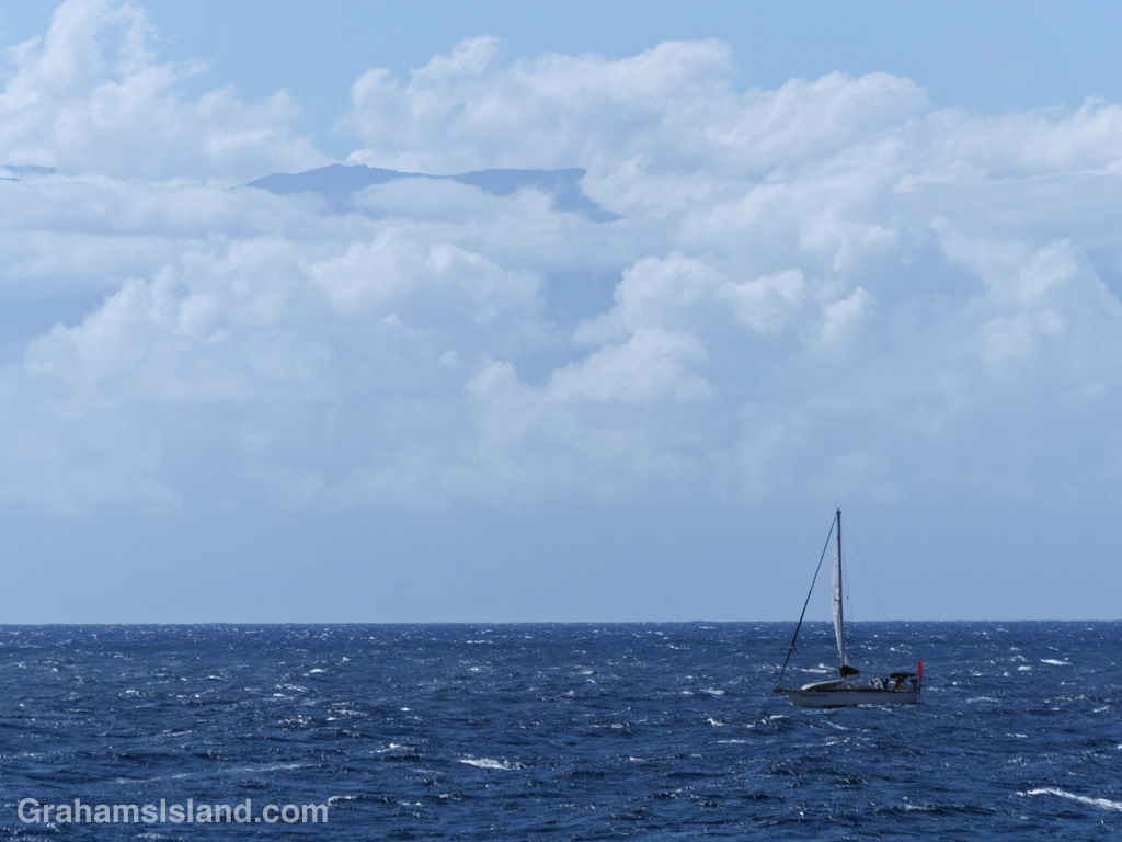 A sailboat rolls down the Alenuihaha Channel under only a mainsail as Maui pokes through the clouds in the background.