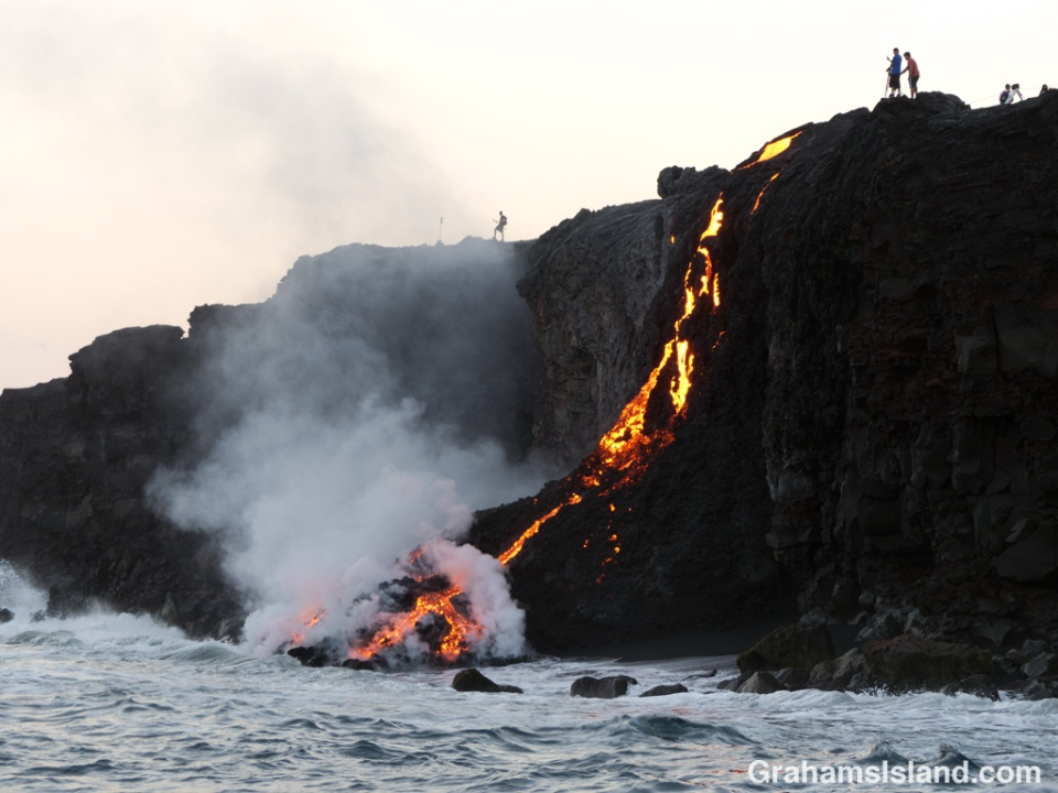 Kilauea lava pours into ocean as people watch from the cliff