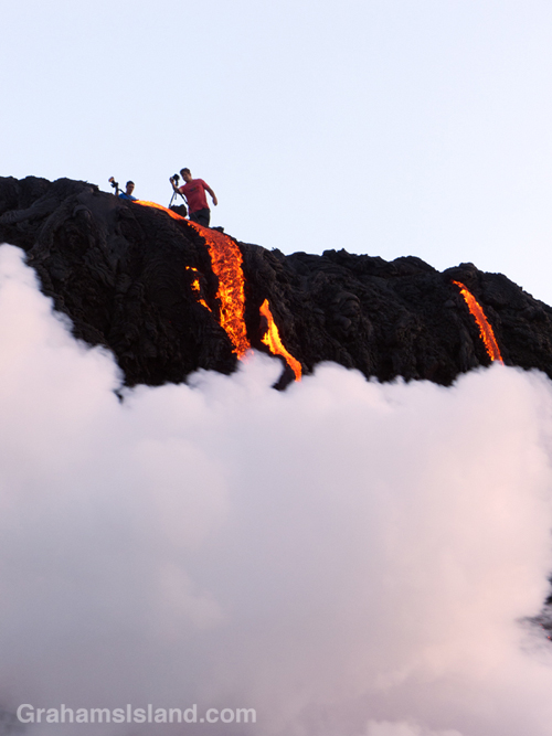 A photographer gets close to the flow as Kilauea lava reaches the ocean.