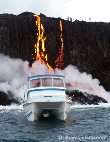 A small boat is on hand to see Kilauea lava reaching the ocean.
