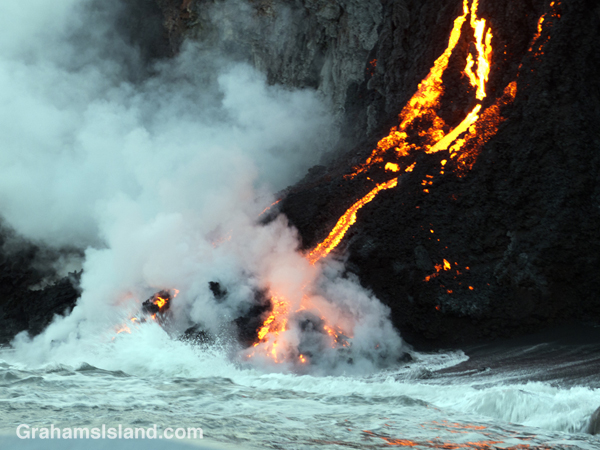 Kilauea lava reaches the ocean with a surge of steam.