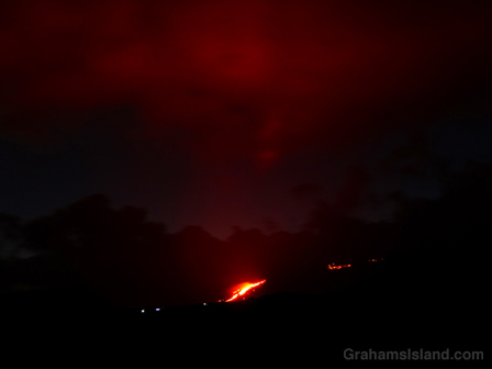 The glow of lava from Kilauea's Pu'u O'o flow reflects off the clouds.