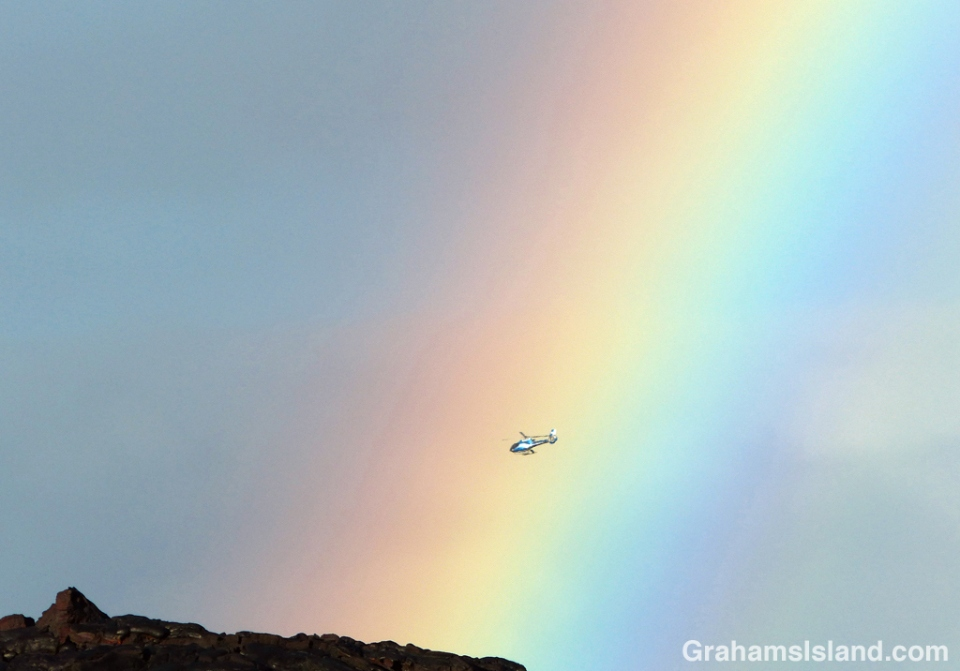 A helicopter passes a rainbow.
