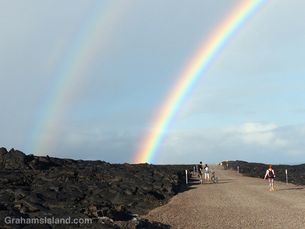 A rainbow rises over the road to the flow from Kilauea Volcano.