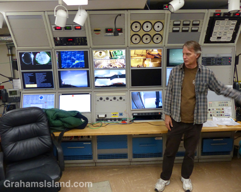 Doug Simons, Executive Director of the CFHT, explains details of the telescope's control room. Note the analog instruments, above and to the left of his head, which register conditions outside the building, a reflection the telescope's late 1970's roots.