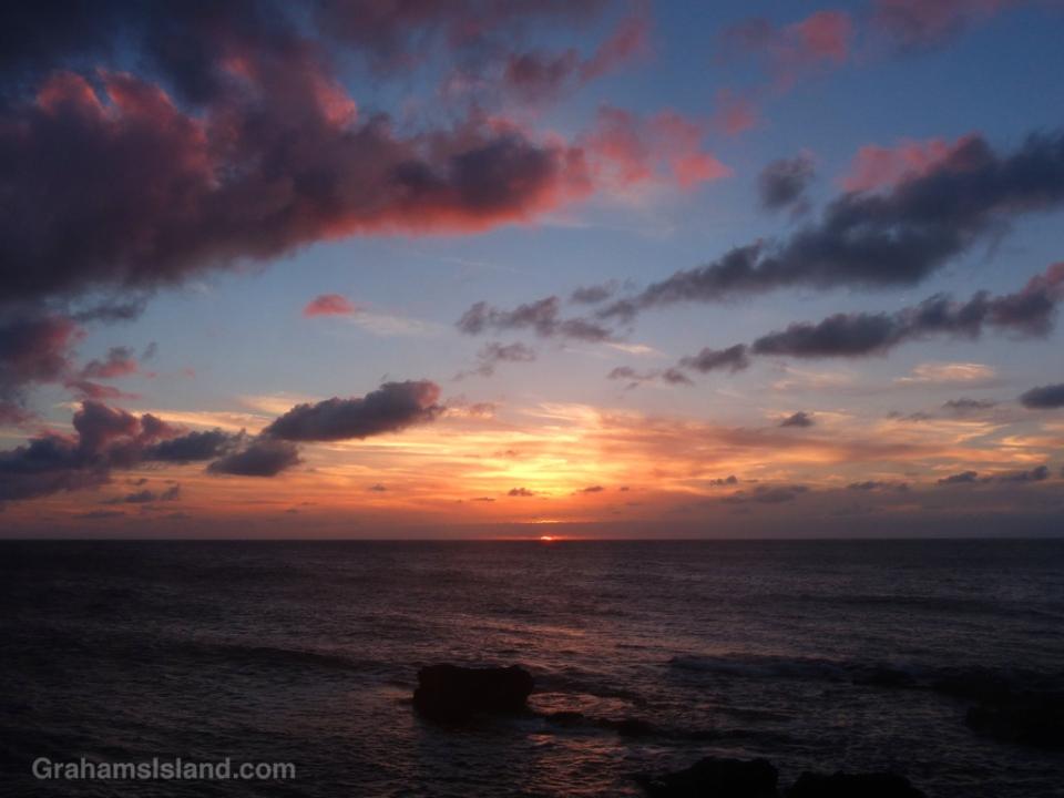 The sun dips below the horizon off Kohala