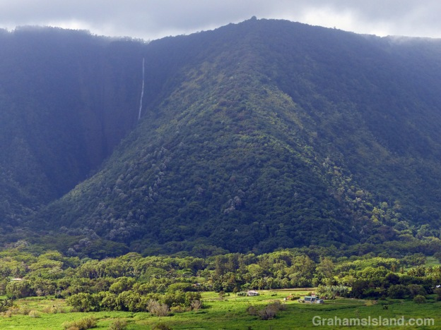 The sun illuminates one of the homesteads in Waipi'o Valley with Hi'ilawe Falls in the background.