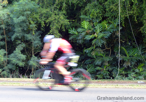 An IRONMAN rider whizzes past tropical foliage on the way out of Hawi