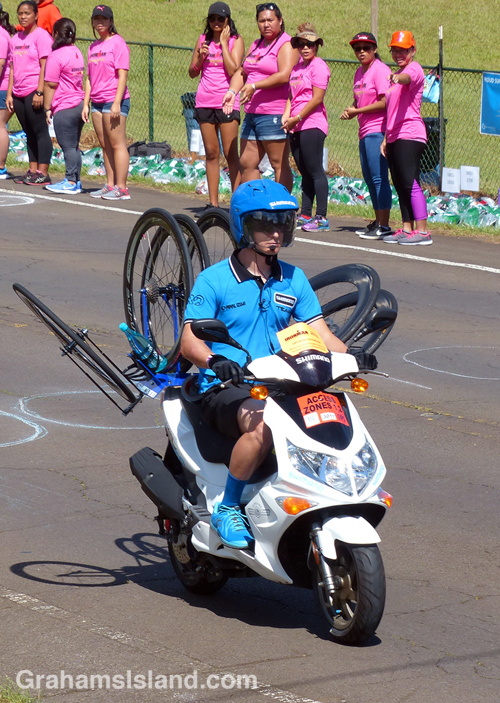A support person carries spare wheels at the IRONMAN world championship on the Big Island.