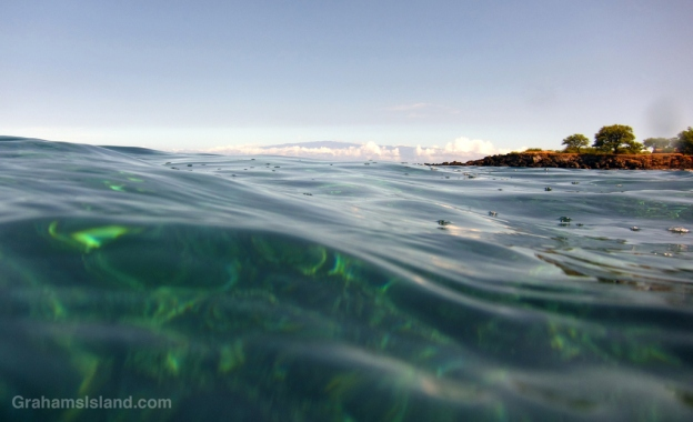 Maui stands out above puffy clouds and long, low swell.