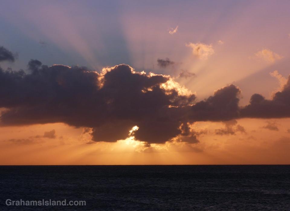 A dark cloud blankets the sun approaching sunset.