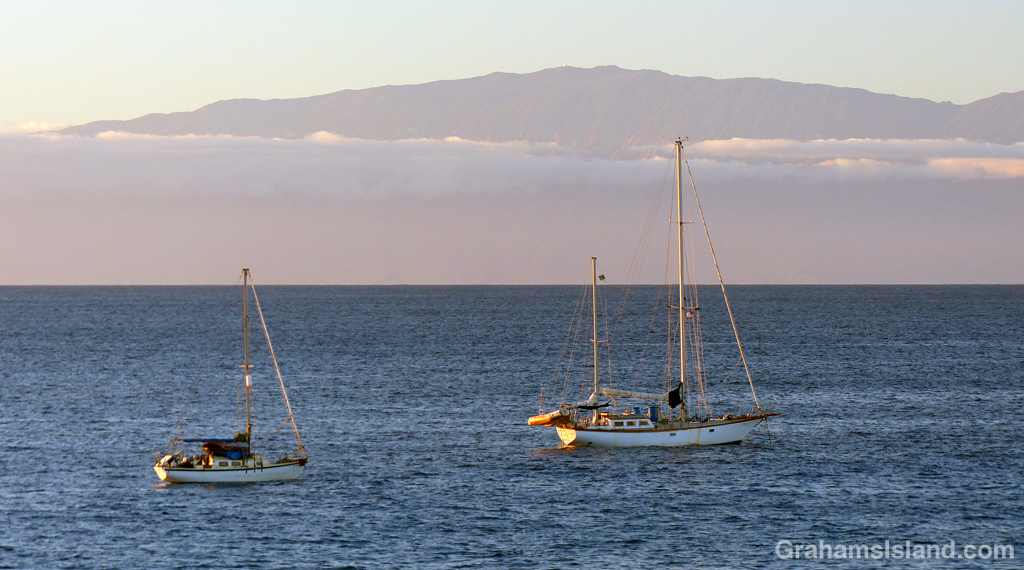 A pair of sailboats at anchor off the Big Island with Maui in the background.