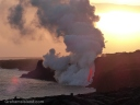 As the sun sinks slowly in the west, a firehose of lava from Kilauea Volcano gushes into the sea.