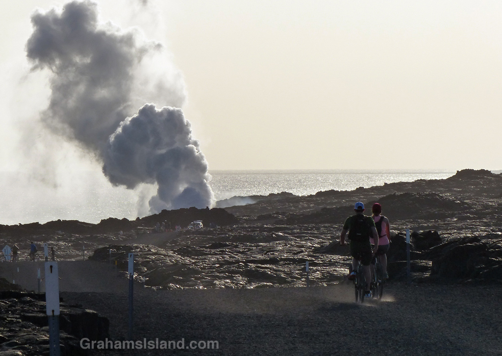 Cyclists head to the Kilauea lava flow where it enters the sea.