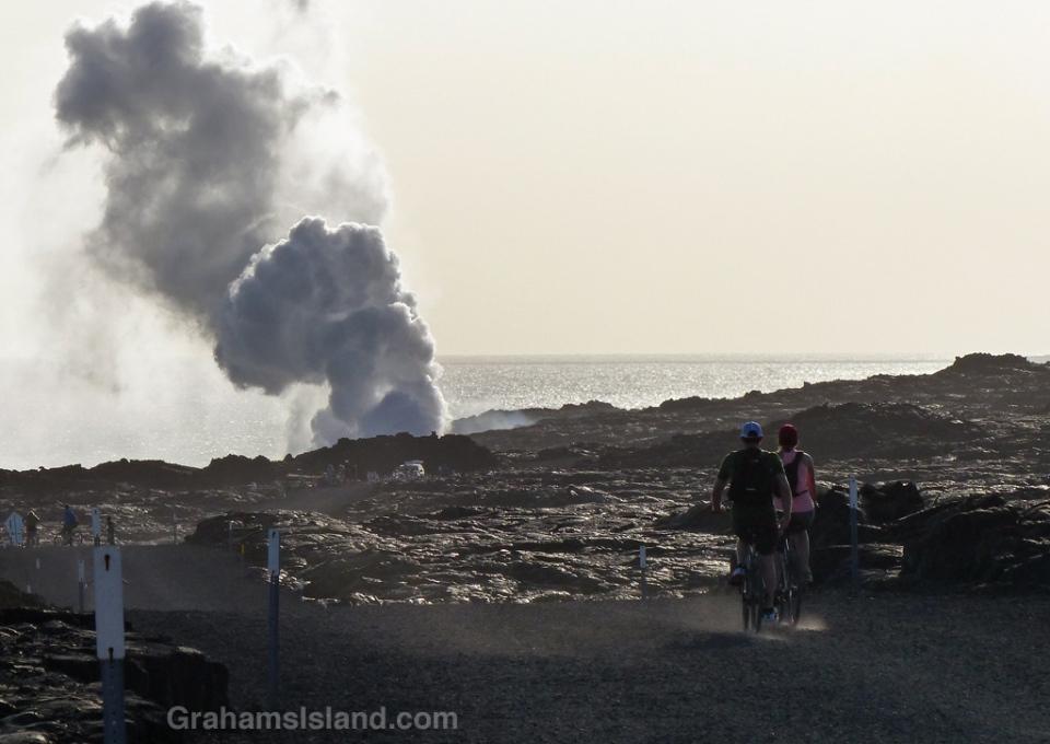Cyclists head to the Kilauea lava flow where it enters the sea.