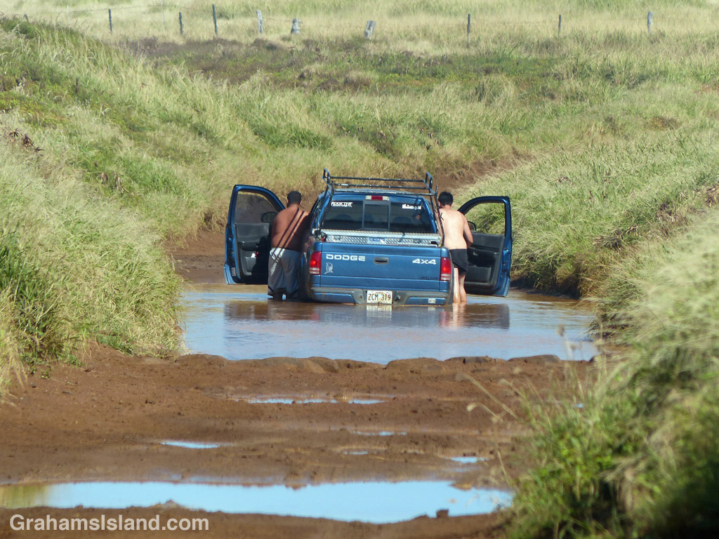 A truck stuck in a muddy puddle on the Big Island of Hawaii
