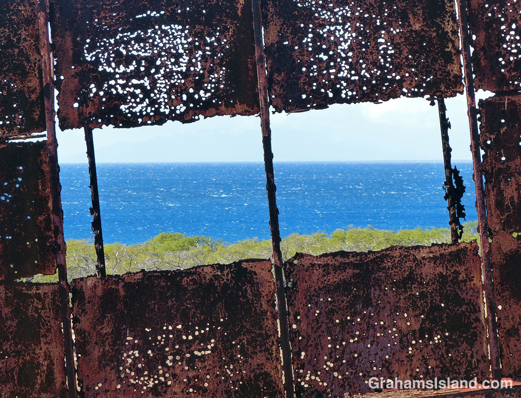 A view of the ocean as seen through a trailer, shot through with rust and perhaps a few bullet holes.
