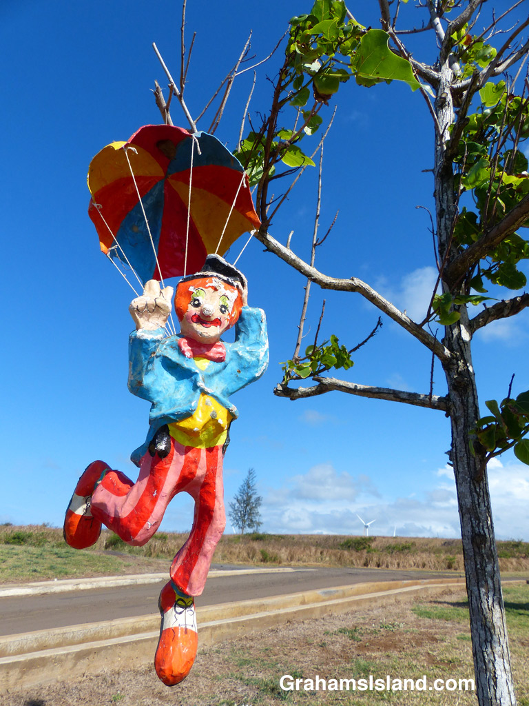 A parachuting clown hangs from a tree.