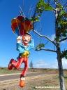 A parachuting clown hangs from a tree.