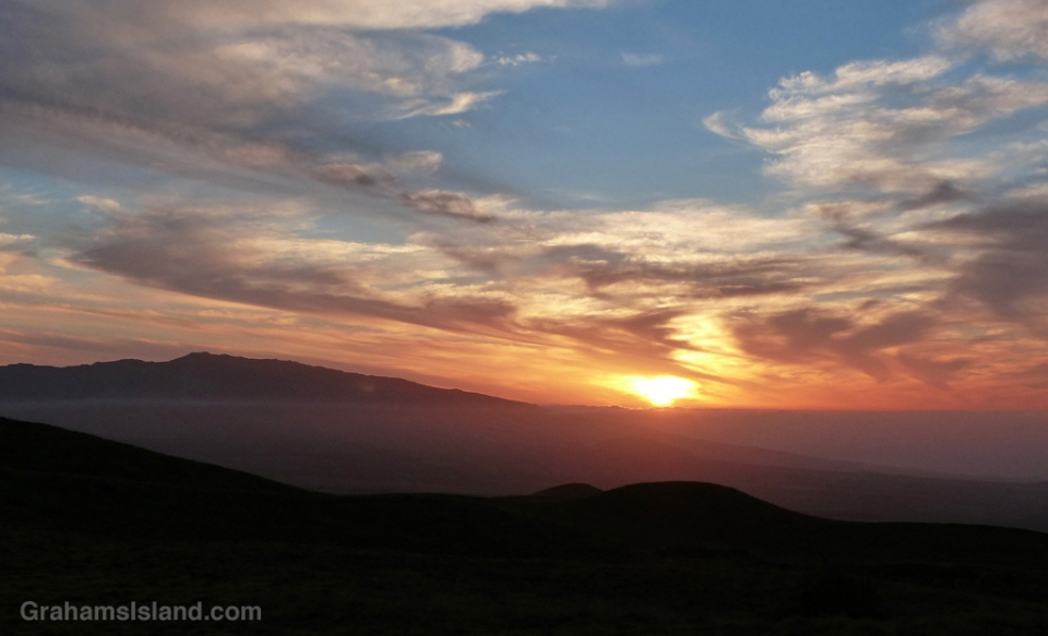 The sun sets off to the side of Hualalai volcano as seen from old Saddle Road on the Big Island of Hawaii