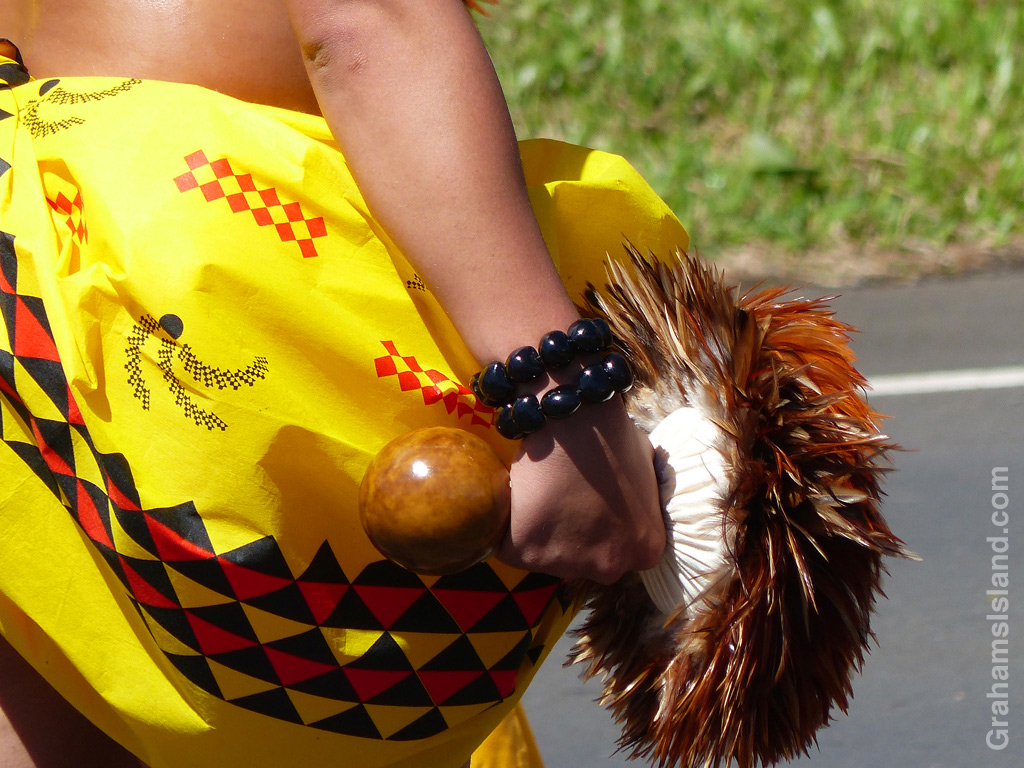 A hula dancer holds a rattle