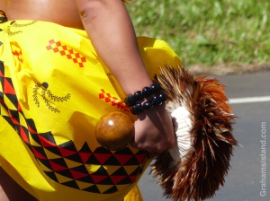 A hula dancer holds a rattle