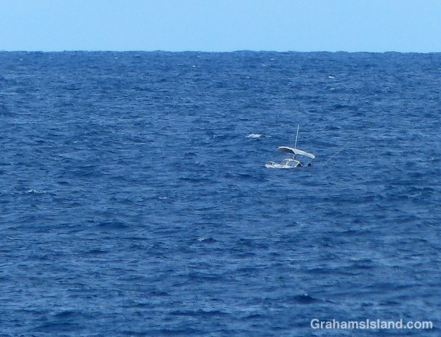 A small boat navigates swells off the Kohala coast.