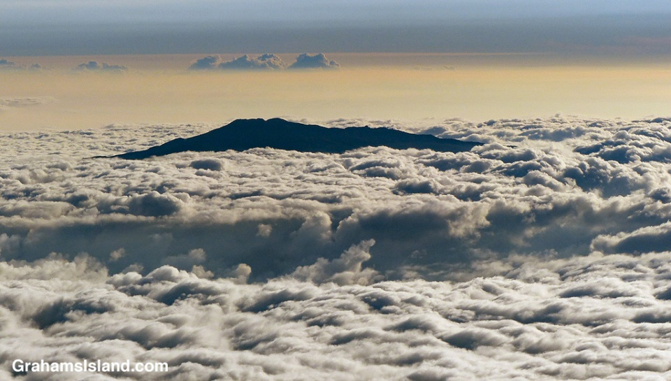 The top of Hualalai Volcano pokes through the clouds on the Big Island of Hawaii.