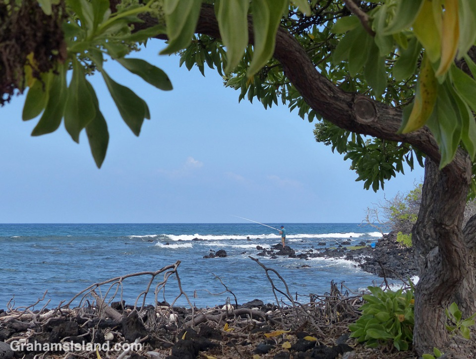 A man tries his luck fishing on the shore of Kaloko-Honokohau National Historical Park north of Kailua Kona.