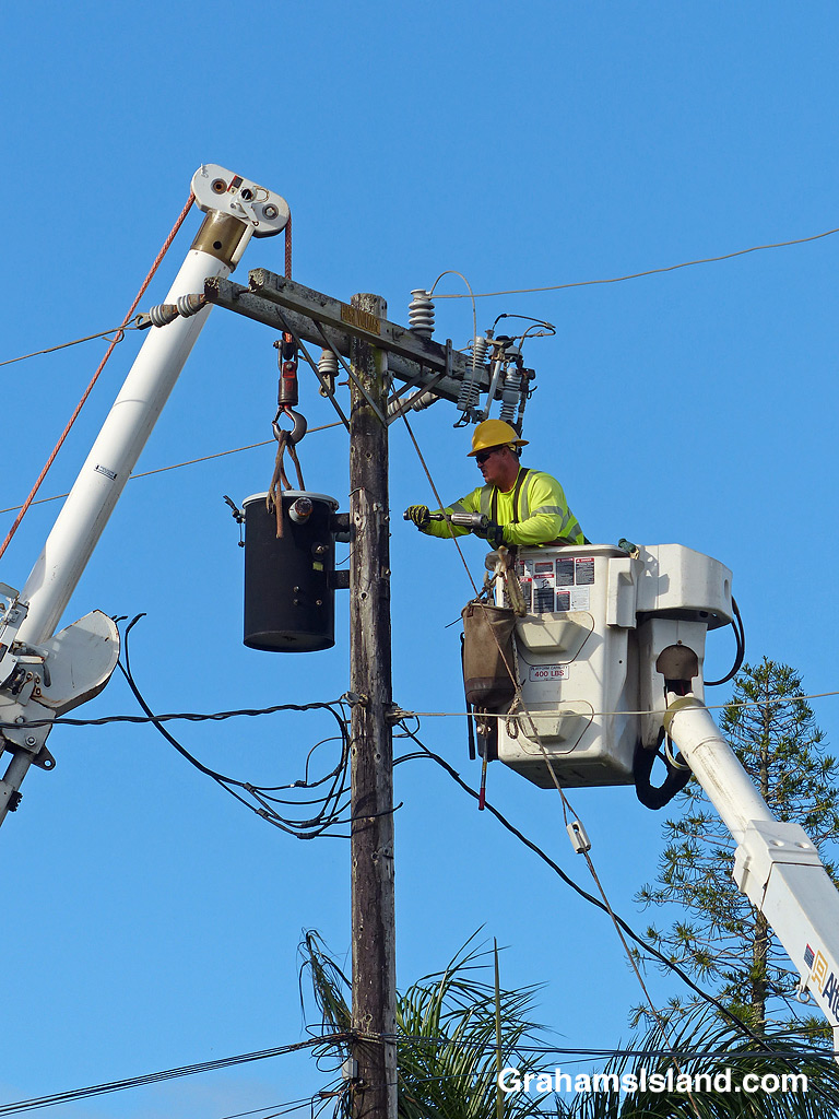 Workers prepare to remove and electrical transformer