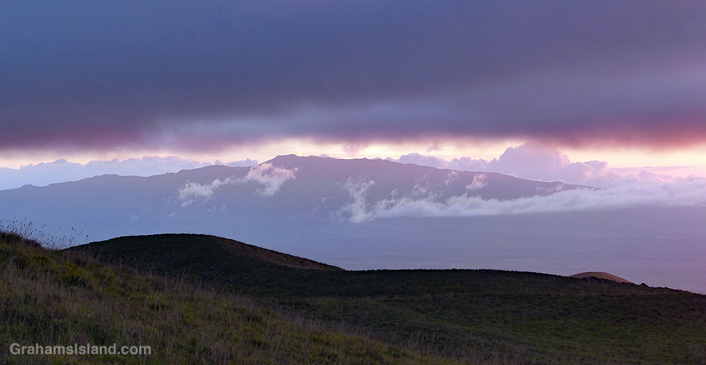 A view of Hualali volcano in the late afternoon sun, sandwiched between the lower slopes of Mauna Kea, in the foreground, and heavy clouds overhead.