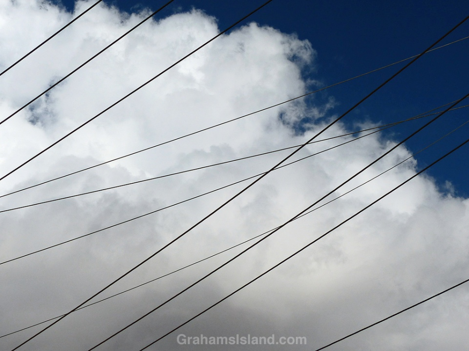 Power lines crisscross beneath fluffy clouds and a deep blue sky.