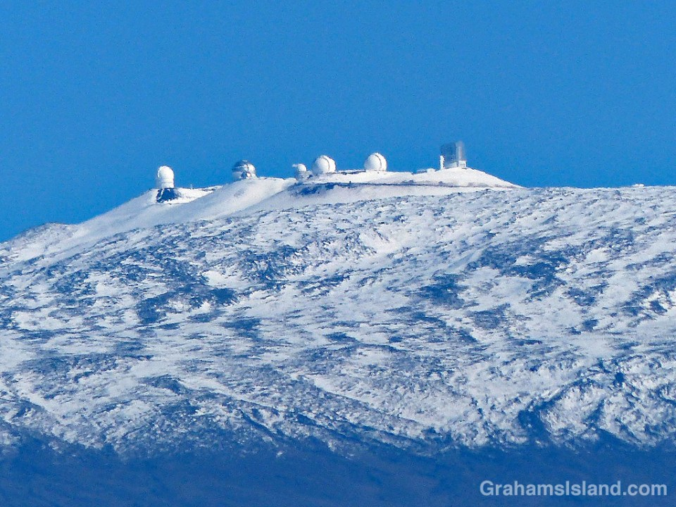 Snow covers the top of Mauna Kea and its telescopes.