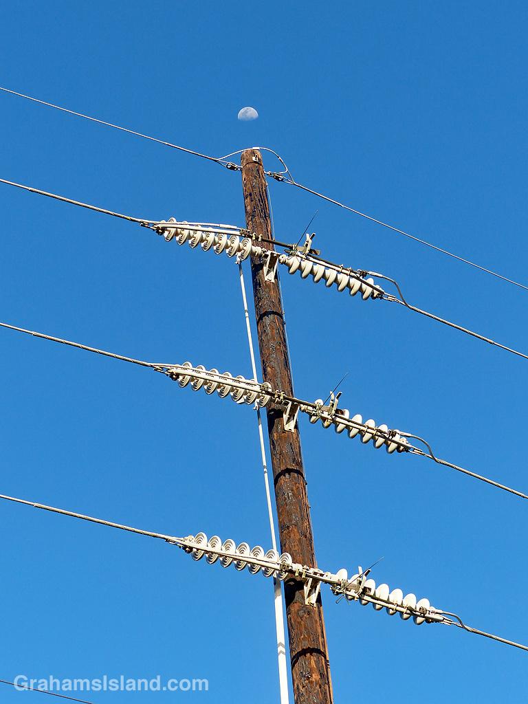 The moon seen above a power pole