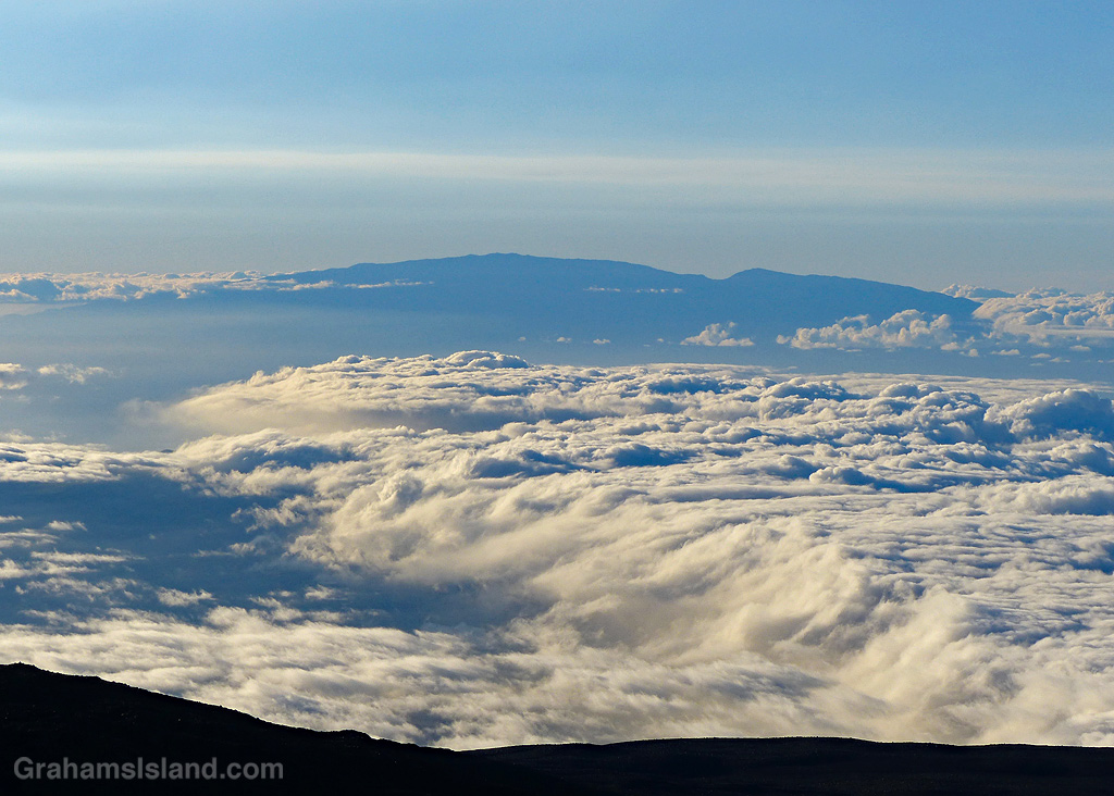 Clouds fill the sky between Mauna Kea and Maui