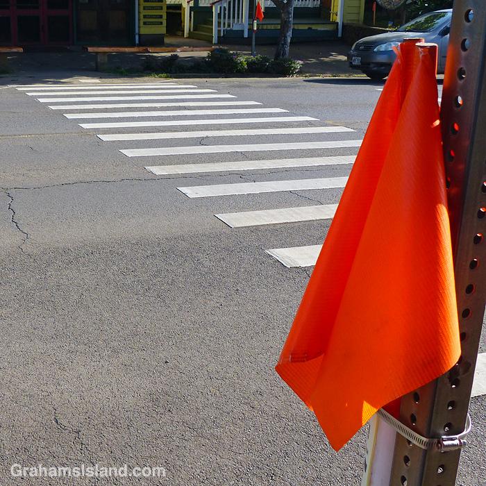 Orange flags by a pedestrian crossing