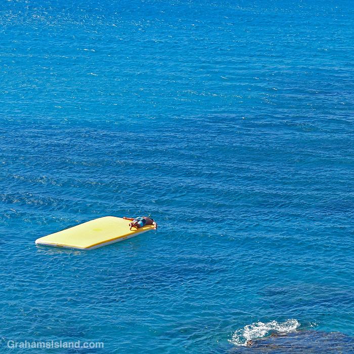 A boy hangs off a yellow raft off the coast of Hawaii