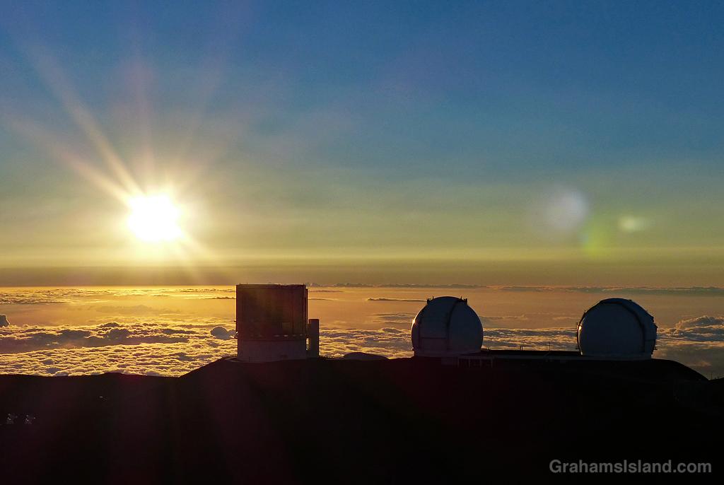 Three telescopes on the summit of Mauna Kea at sunset