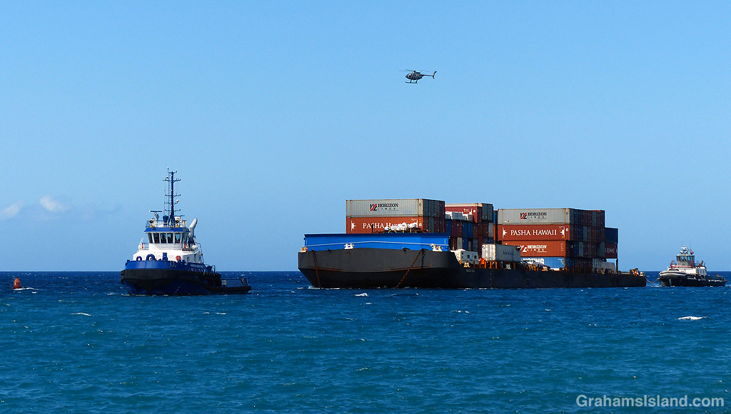 A tug and barge enters Kawaihae Harbor in Hawaii