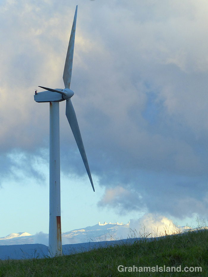 A wind turbine with snow covered Mauna Kea in the background