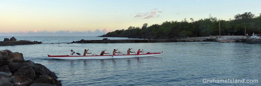 An outrigger canoe entering harbor in Hawaii