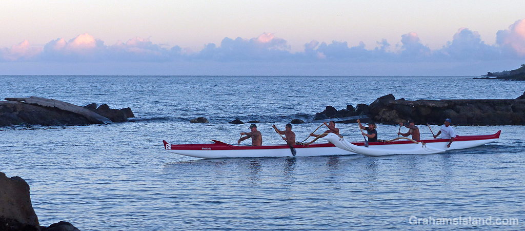 An outrigger canoe leaving harbor in Hawaii